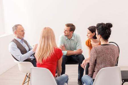 経験豊かな心理学者グループのコンサルティングです。彼が座っていると、真剣に何かを説明します。男性と女性は注意深く彼に聞いています。