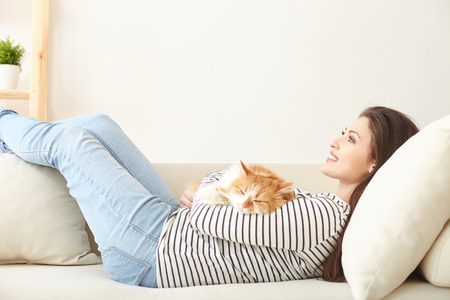 pet cat: Pretty young woman is enjoying time at home. She is lying on sofa and holding a cat. The lady is smiling and looking forward dreamingly Stock Photo