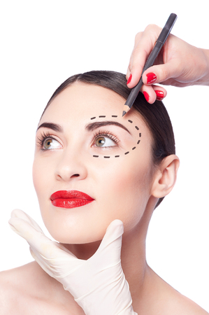 imaginary line: Portrait of beautiful girl doing facial make-up. Hand of beautician is drawing her eyebrow with a pencil. The lady is calm and relaxed. There is imaginary line over her eye Stock Photo
