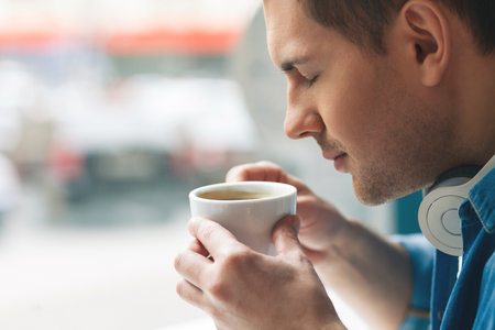 Handsome young man is drinking a cup of coffee. He closed his eyes with pleasure. Copy space in left side