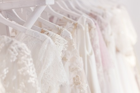 랙에 걸려있는 하얀 웨딩 드레스의 닫습니다