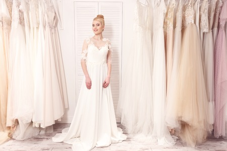 bridal salon: Pretty future bride is preparing for wedding. She is standing near variety of clothing hanging on rack. The lady is looking at camera and smiling