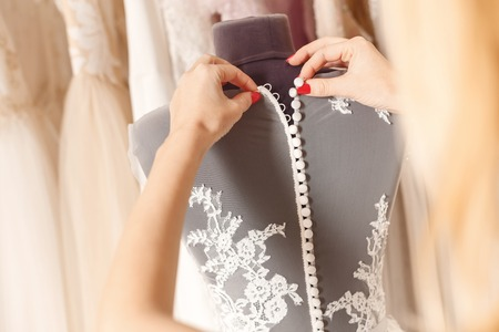 Close up of arms of designer buttoning wedding dress on mannequin