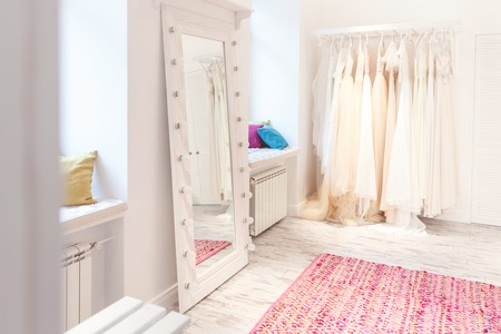 bridal salon: Collection of wedding dresses and big mirror in showroom
