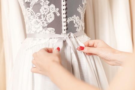 Cerca de las manos femeninas que ajustan el arco en la parte posterior de la ropa de la boda Foto de archivo