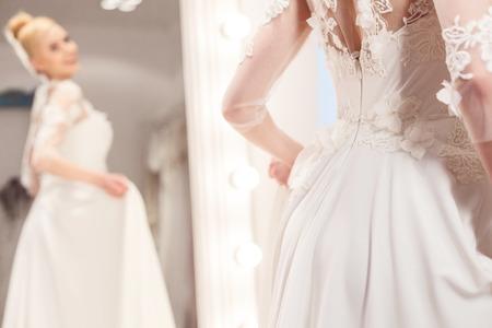 A noiva futura alegre está fazendo a experimentação de um vestido de casamento. Ela está de pé e posando perto do espelho. A menina está sorrindo feliz