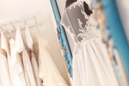 Mooie trouwjurk van mannequin in atelier. Diverse bruids kleding in opknoping op de achtergrond