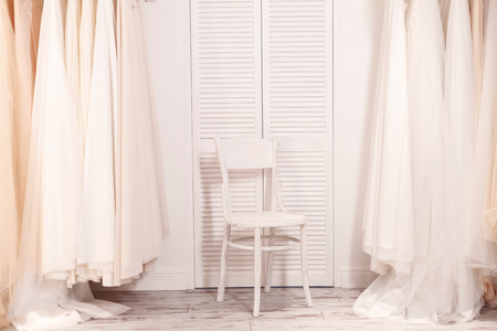 bridal salon: White chair between wedding dresses in boutique Stock Photo