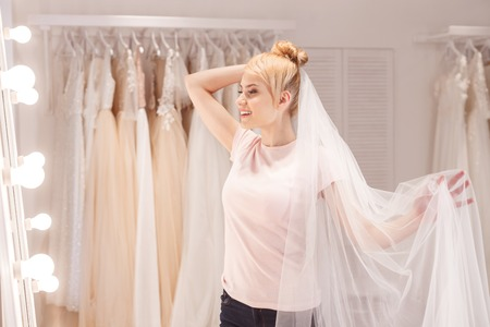 Beautiful young woman is trying on bridal veil. She is standing and looking at mirror dreamingly. The lady is smiling Stock Photo