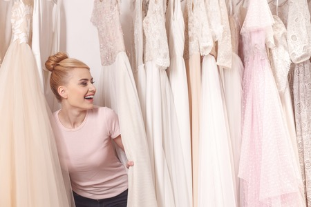Pretty young woman is hiding between wedding dresses in boutique. She is laughing with happiness