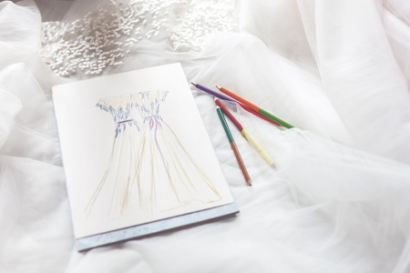 white cloth: Close up of sketch of wedding dress near pencils on white cloth Stock Photo