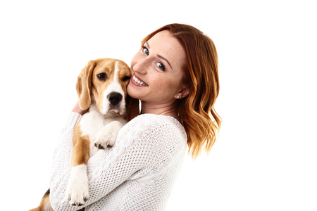 beagle puppy: Attractive girl is playing with puppy. She is holding and hugging the animal. The lady is standing and smiling. Isolated and copy space in right side