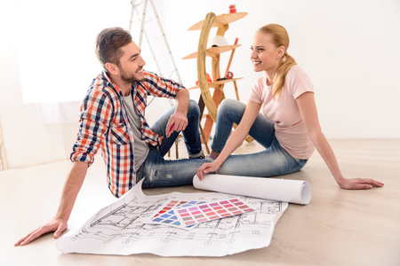 furnish: It only begining. Smiling young couple dreaming how they will furnish apartment, sittin on floor their new house and looking each other