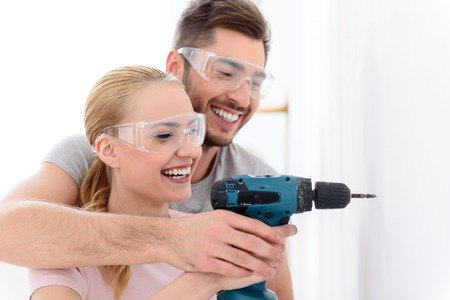 hands work: Drilling through the drywall. Smiling man and woman together making hole in white wall, using drill in special protective glasses