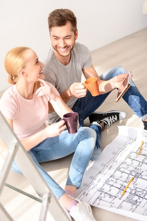 in loving memory: I like your offer. Top view of happy couple sitting on the floor, drinking coffee and selecting ideas for repair using tablet Stock Photo