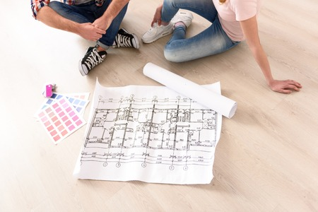 getting started: Getting started. Closeup of couple looking at construction house plan with color palette, sitting on floor