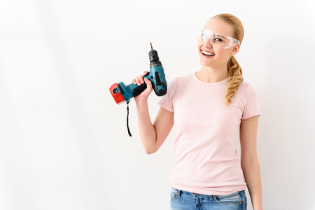 protective glasses: She handy with drill. Attractive young handy woman holding drill isolated on white background in in special protective glasses