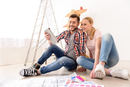 redecorate: So many variants. Young couple in love moving in new apartment, sitting on the floor, planning to redecorate their new home, using tablet