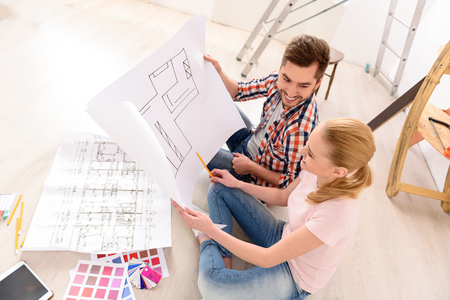 in loving memory: Planning always interesting. Top view of smiling couple having fun deciding on paint colour swatch for new home apartment