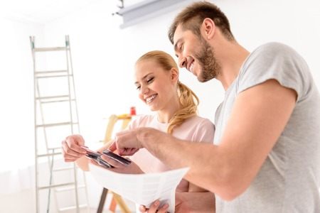 picks: Always hard to choose. Happy smiling couple making repairs in their apartment and picks up color of walls, using palette of colors