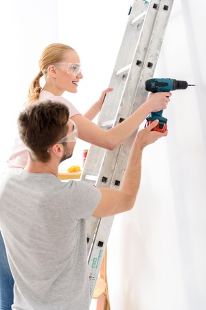 making hole: Doing hard man job. Young guy helping girl keeping drill and making hole in white wall, standing on ladder, in special protective glasses Stock Photo