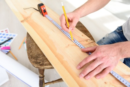 exactness: This work takes precision. Top view of man working with plank of wood using tape measure, making repairs in the apartment Stock Photo