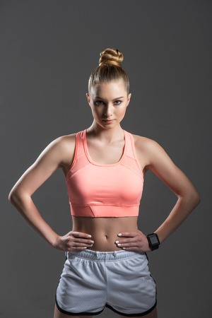 arms akimbo: Portrait of beautiful young woman with athletic figure. She is standing with arms akimbo and looking at camera confidently. Isolated Stock Photo