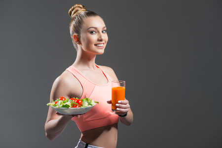 to prefer: I prefer healthy diet. Waist up portrait of attractive slim sporty woman holding a plate of salad and glass of juice. She is standing and smiling. Isolated and copy space in right side