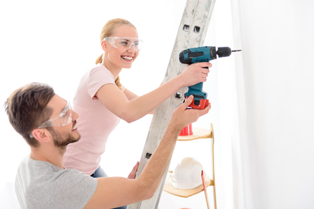 making hole: Together always much easier. Young smiling man helping girl standing on stepladder, keeping drill and making hole in white wall
