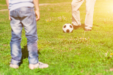 affectionate actions: Close up of feet of old man kicking the football ball to his grandchild. The boy and grandfather are standing on grass