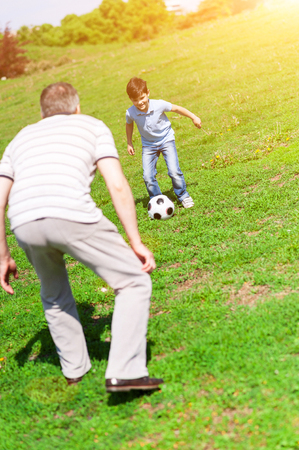 affectionate actions: Happy boy and his grandfather are playing football in park. The child is kicking the ball and smiling