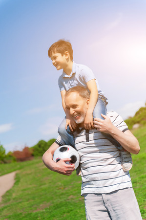 affectionate actions: Cheerful old man is playing with his grandson in park. He is holding a boy on his shoulders and the football ball. They are smiling Stock Photo