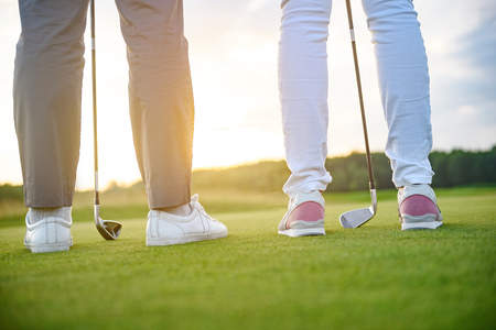 drivers: Ready to play golf. Close up of two golfers ready to tee off on golf field, holding drivers