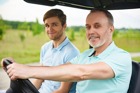 Consumables: Golfing with my father. Close up of father and son enjoying day on golf course, driving cart Stock Photo