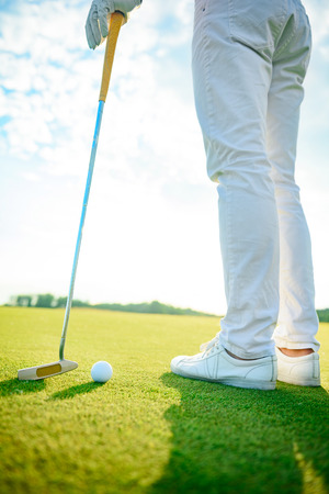 long day: It will be long day on course. Close up of golfer standing on course and holding driver during sunny day Stock Photo