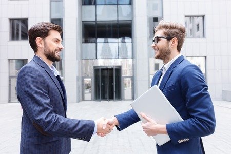 acquaintance: Successful two businessmen are shaking hands by acquaintance. They are standing outdoors and smiling. Young man is holding a laptop Stock Photo