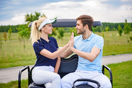 satisfying: It was great golfing with you. Smiling young golfing couple giving each other hi-five after satisfying round of golf, looking at each other
