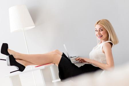 Nette junge Frau schreibt auf Laptop im Büro . Sie steht und hält ihre Beine auf dem Tisch . Sie entspannt die Kamera und betrachtet sie lacht