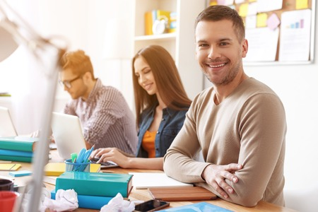 studing: Having study partners is great. Smiling young student studing using books and laptop with friends in background Stock Photo