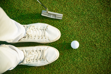 staying: One shot to success. Top view of golfer staying near white ball, holding driver
