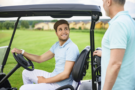 cart: Discussing handicaps. Smiling son talking with his father on their way to tee-off, driving golf cart