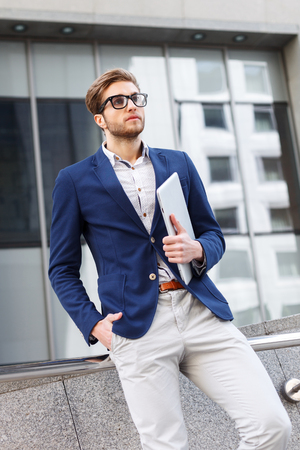 seriousness: Handsome young businessman is standing outdoors and holding a notebook. He is looking forward with seriousness. The worker is wearing suit and eyeglasses Stock Photo