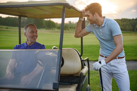 golfing: Golfing buddies. Smiling mature golfer seating in golf cart with her partner standing alongside Stock Photo