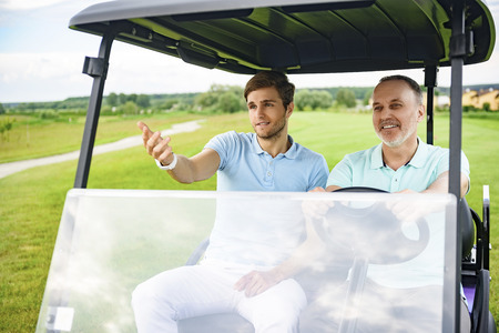 game drive: Out for drive. Two men driving golf cart along golf field, discussing upcoming game