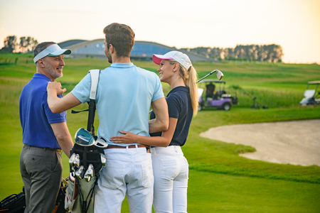 copyspace: Attractive golfers. Smiling golfing companions standing on golf course and looking each other with golf cart on background Stock Photo