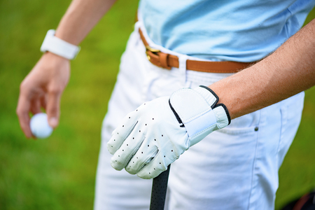 let go: Let go golfing. Close up of hands of male golfer, holding golf ball in one and golf club in another