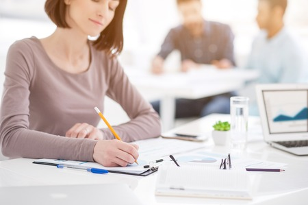 strategizing: Teamwork in action. Close up of young office worker sitting at table with colleagues in the background and making notes in notebook
