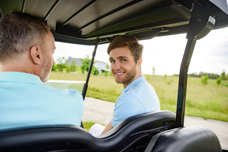 cart: Carting it around course. Close up of happy young guy driving a golf cart, sitting next to his father