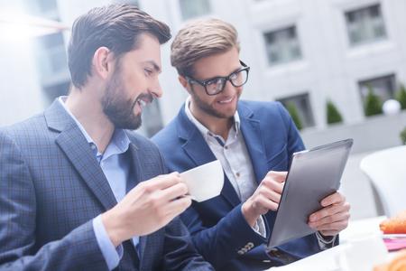 El éxito de socios de negocios jóvenes están trabajando en nuevo proyecto en conjunto. Se están fijando en la tableta y sonriendo con satisfacción. Los hombres están sentados en la mesa en el restaurante y el consumo de café Foto de archivo - 58173395
