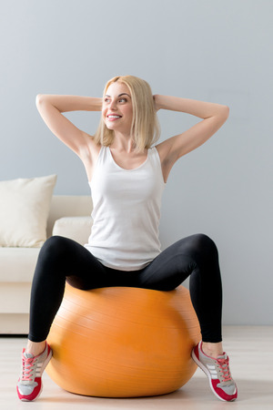 arms behind head: Attractive young woman is sitting on fitness ball and doing exercise. She is raising arms behind her head. The lady is looking aside and laughing